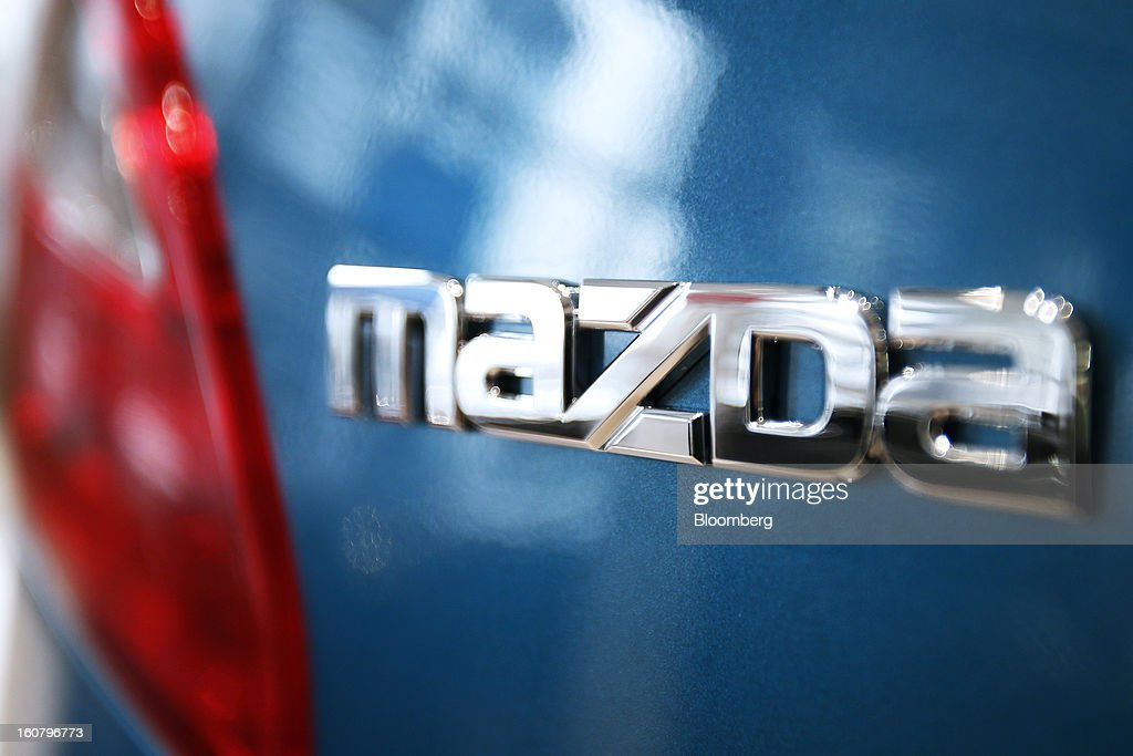 Signage for Mazda Motor Corp. is displayed on a Demio compact vehicle at the company's showroom in Tokyo, Japan, on Wednesday, Feb. 6, 2013. Mazda, the best performer on the Nikkei 225 Stock Average in the past three months, more than doubled its full-year profit forecast on a weaker yen and demand for its fuel-efficient vehicles. Photographer: Kiyoshi Ota/Bloomberg via Getty Images
