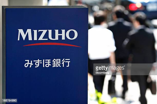 Signage for Mizuho Bank Ltd is displayed as pedestrians walk past a branch in Tokyo Japan on Wednesday May 15 2013 Japan's three biggest banks led by...