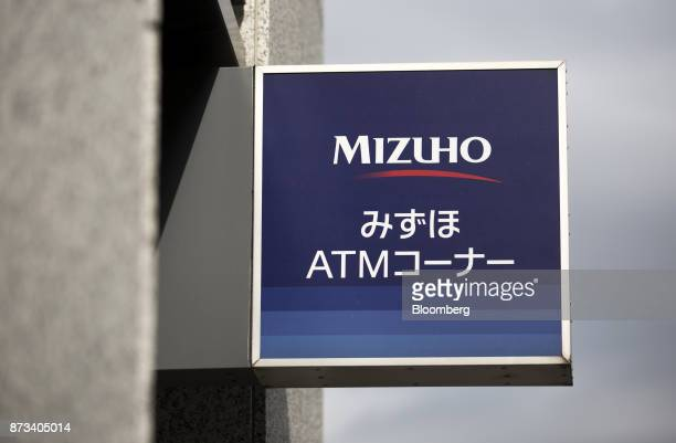 Signage for Mizuho Bank Ltd's automated teller machines is displayed outside one of the company's branches in Tokyo Japan on Friday Nov 10 2017...