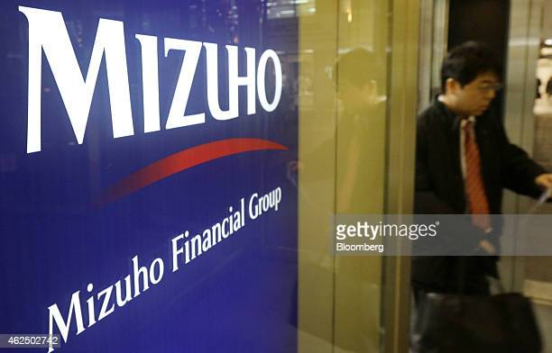 Signage for Mizuho Financial Group Inc is displayed outside a Mizuho Bank Ltd branch in Tokyo Japan on Thursday Jan 29 2015 Mizuho Financial Group...