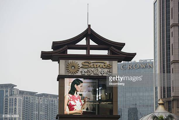 Signage for Sands Macau hotel operated by Sands China Ltd stands in front of Studio City casino resort developed by Melco Crown Entertainment Ltd...