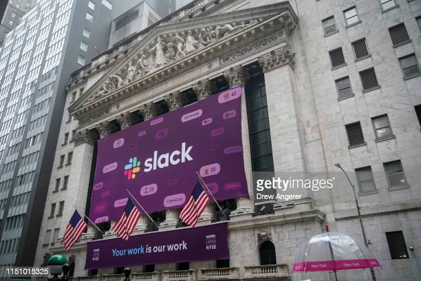 Signage for Slack is displayed on the outside of the New York Stock Exchange , June 20, 2019 in New York City. The workplace messaging app Slack will...