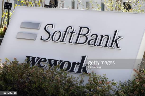 Signage for SoftBank Corp. And WeWork Companies Inc. Outside an entrance leading to SoftBank Group's headquarters at the Tokyo Portcity Takeshiba...
