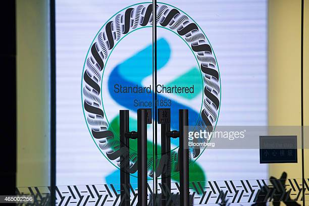 Signage for Standard Chartered Plc is displayed on the door of a bank branch in the Central district of Hong Kong China on Monday March 2 2015...