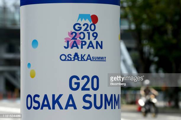 Signage for the 2019 Group of 20 Summit is displayed on a pole in Osaka, Japan, on Saturday, June 22, 2019. Central bankers hand back the spotlight...