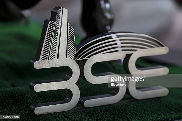 Signage for the Bombay Stock Exchange is displayed next to a bronze bull statue at the entrance to the BSE building in Mumbai India on Monday June 27...