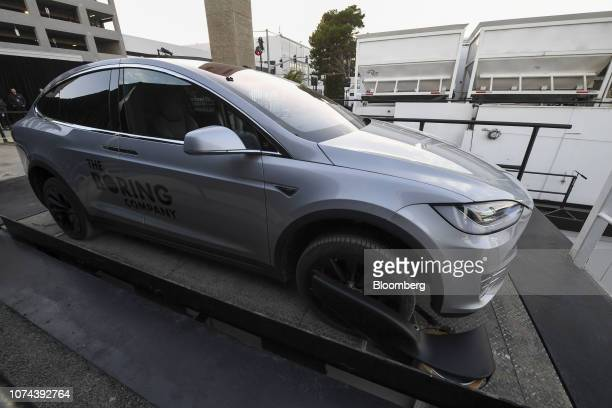 Signage for the Boring Co. Is displayed on a modified Tesla Inc. Model X vehicle sitting on an elevator near the pit and tunnel entrance prior to an...