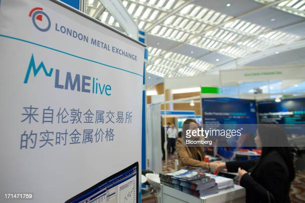 Signage for the London Metal Exchange LMElive the exchanges realtime price and data system stands on display during the LME Week Asia 2013 Seminar in...