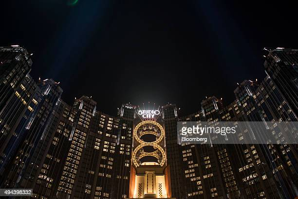 Signage for the Studio City casino resort is illuminated atop the resort, developed by Melco Crown Entertainment Ltd., at night in Macau, China, on...