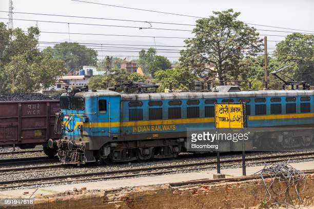 Signage for Tori Junction stands as a locomotive passes through the Tori Siding on the ToriShivpur rail line operated by Indian Railways and funded...