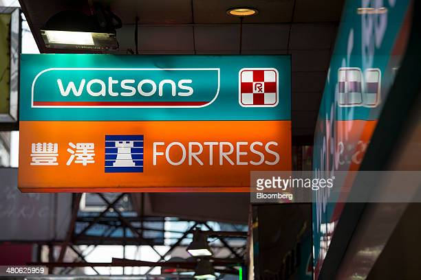 Signage for Watsons and Fortress stores both operated by AS Watson Co are displayed outside the stores in Hong Kong China on Tuesday March 25 2014...