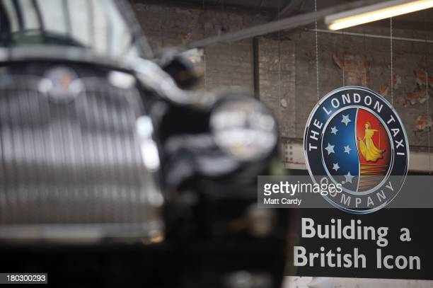 Signage hangs inside the factory of The London Taxi Company beside a completed TX4 London Taxi cab on September 11 2013 in Coventry England The...