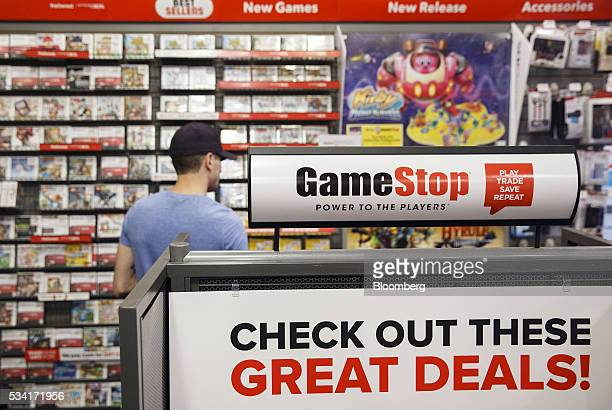 Signage is displayed as a customer browses video games at a GameStop Corp store in West Hollywood California US on Sunday May 22 2016 GameStop Corp...