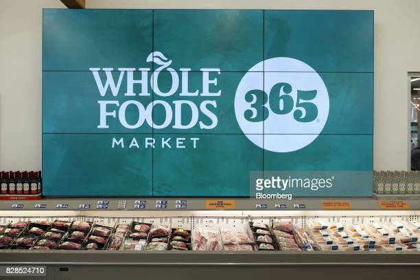 Signage is displayed on a video board above meat and seafood during the grand opening of a Whole Foods Market 365 location in Santa Monica California...