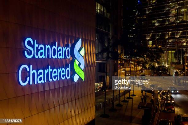 Signage is illuminated atop a Standard Chartered Plc bank branch at night in Hong Kong China on Thursday July 25 2019 Standard Chartered is scheduled...