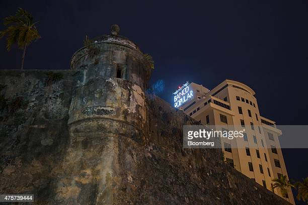 Signage is illuminated on the Banco Popular building near the wall that surrounds Old San Juan Puerto Rico on Friday May 29 2015 For the hedge funds...