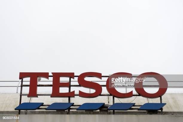Signage is pictured at a branch of Tesco in south London on January 9 2018 / AFP PHOTO / Justin TALLIS