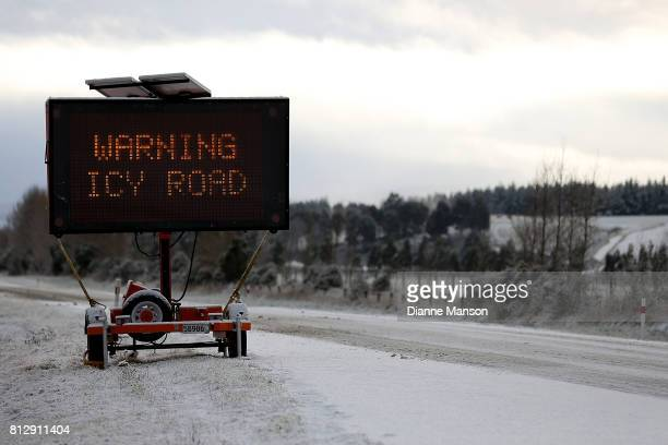Signage is placed roadside to warn drivers of the icy road conditions ahead on July 12 2017 in Invercargill New Zealand Snow is falling across the...