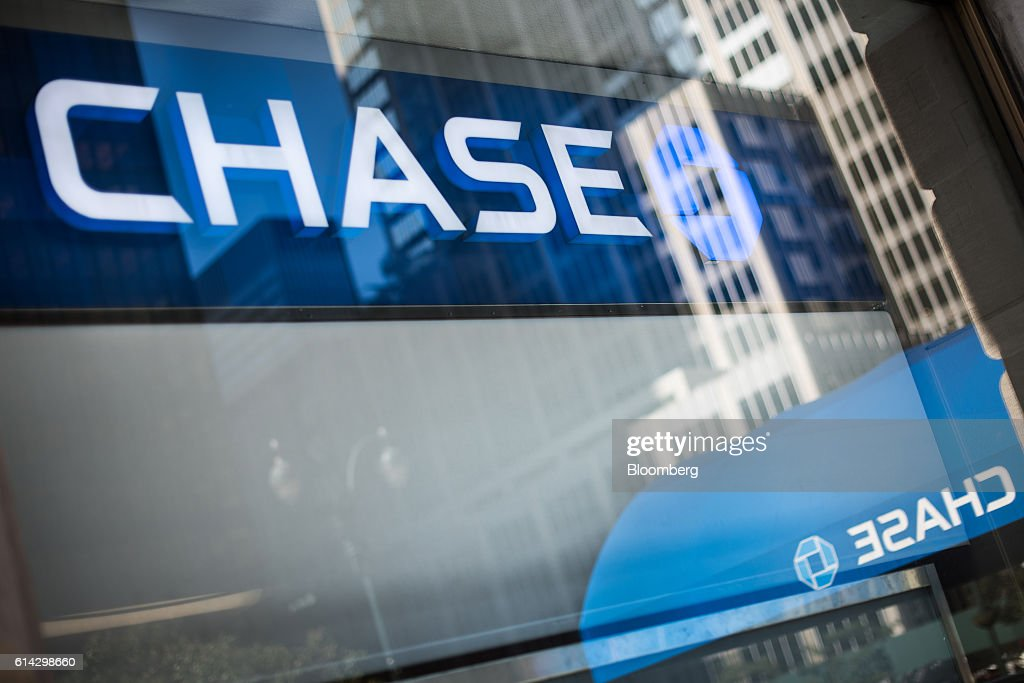 Signage is reflected in the window of a JPMorgan Chase & Co. bank branch in New York, U.S., on Friday, Oct. 7, 2016. JPMorgan Chase & Co. is scheduled to release earnings figures on October 14. Photographer: Mark Kauzlarich/Bloomberg via Getty Images