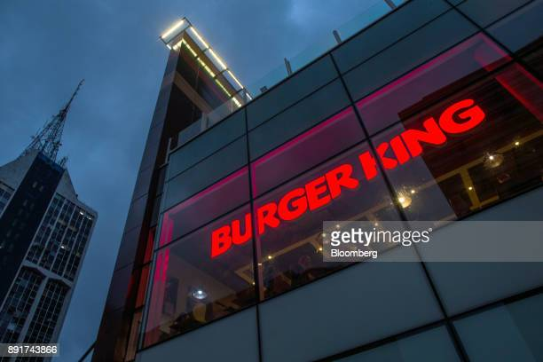 Signage is seen illuminated at night in the window of a Burger King do Brasil restaurant on Paulista Avenue in Sao Paulo, Brazil, on Monday, Dec. 11,...
