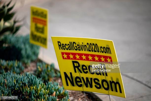 Signage is seen near a booth where conservative activists gather signatures in a recall effort against California Governor Gavin Newsom near Pasadena...