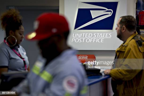 Signage is seen past customers and a postal clerk left at the United States Postal Service Joseph Curseen Jr and Thomas Morris Jr post office station...