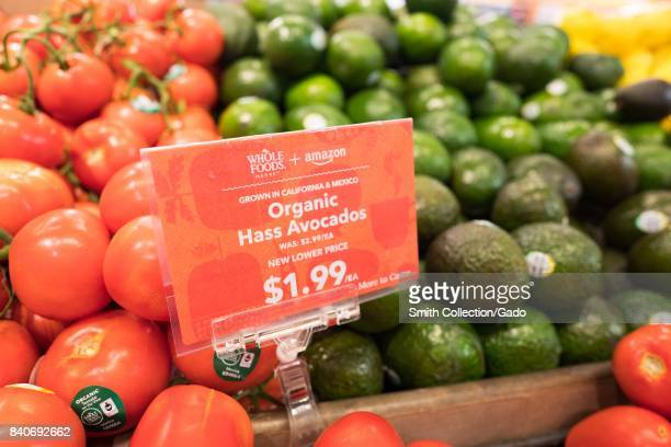 Signage on a display of avocados at the Whole Foods Market store in Lafayette California reading 'Whole Foods Market and Amazon New Lower Price More...