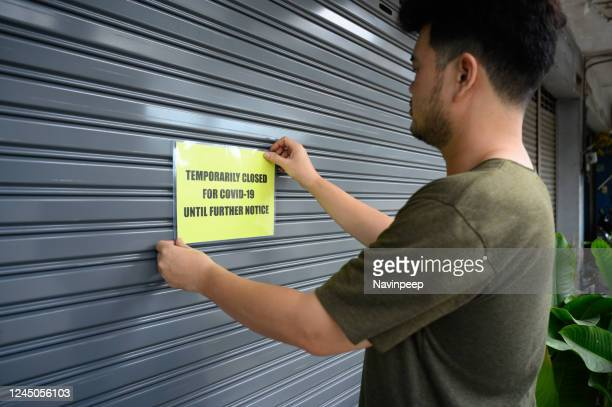 signage on door, temporarily closed for covid-19 until further notice, metal shutter - closing stock pictures, royalty-free photos & images