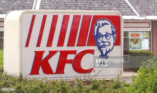 Signage promoting new oven roasted menu items is visible beyond KFC signage at a KFC restaurant May 10 2004 in Mount Prospect Illinois KFC...