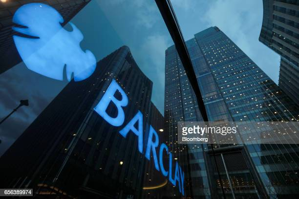 Signage shines through a window reflecting Barclays Plc head offices at the Canary Wharf business financial and shopping district in London UK on...
