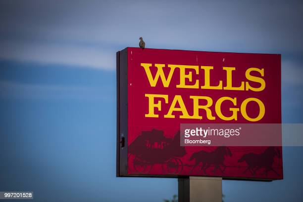 Signage stands on display outside a Wells Fargo Co bank branch in Niles Illinois US on Tuesday July 10 2018 Wells Fargo Co is scheduled to release...