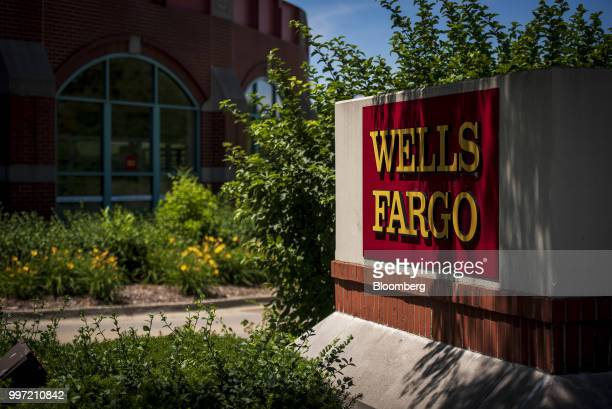 Signage stands outside a Wells Fargo Co bank branch in Schaumburg Illinois US on Tuesday July 10 2018 Wells Fargo Co is scheduled to release earnings...