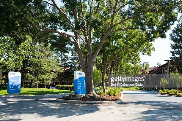 Signage with logos near a treelined driveway at the headquarters of financial software company Intuit in the Silicon Valley town of Mountain View...