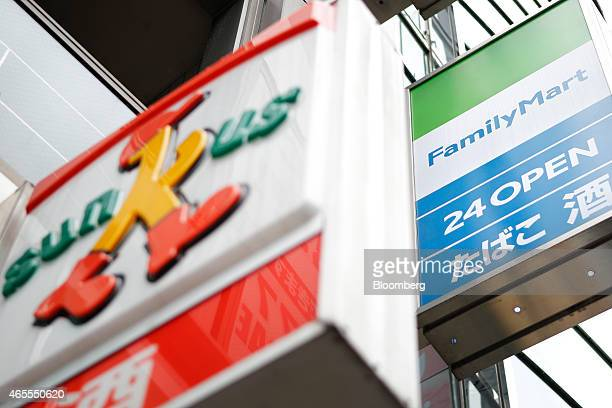 Signages for FamilyMart Co convenience store right and Sunkus convenience store operated by Uny Group Holdings Co subsidiary Circle K Sunkus Co are...