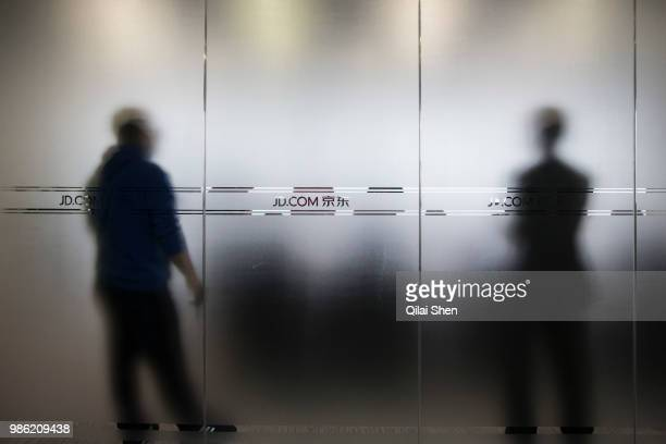 Signages for JDcom Inc are displayed on a pane of glass of a conference room at JDcom's headquarters in Beijing China on Monday Nov 30 2015 JDcom is...
