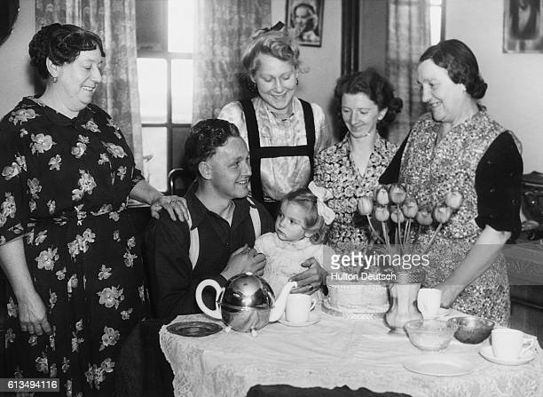 Signalman Alf Fitzgerald celebrates his reunion with his family after spending five years in a German prisoner of war camp His mother cuts the...