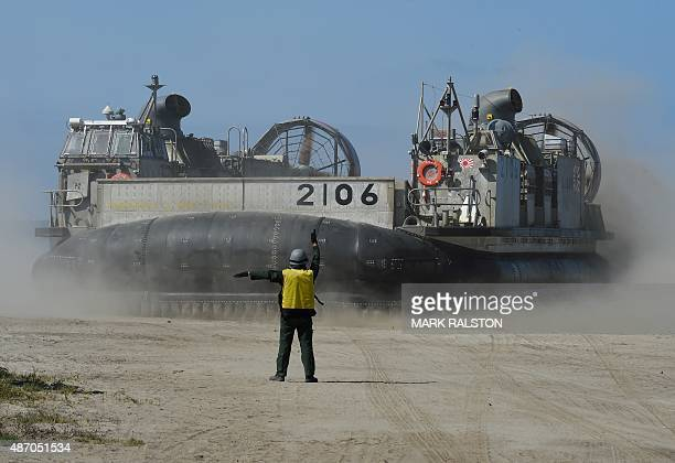 A signalman directs a Japanese Landing Craft Air Cushion hovercraft during an amphibious landing operation with US Forces and the Japan Maritime...