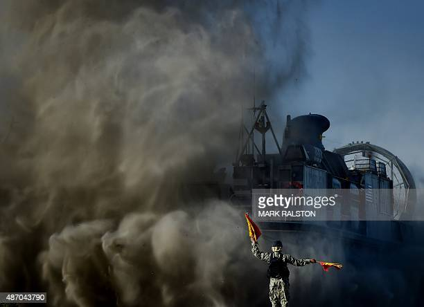A signalman directs a US Marines Landing Craft Air Cushion hovercraft during an amphibious landing operation with the Japan Maritime SelfDefense...
