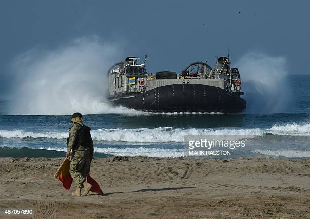 A signalman directs a US Marines Landing Craft Air Cushion hovercraft during an amphibious landing operation with US Forces and the Japan Maritime...