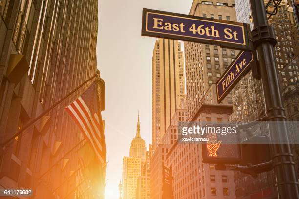 Signboard and Empire State Building during sunset