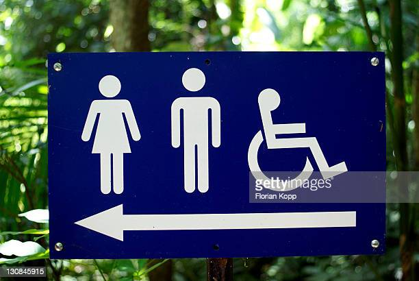 Signboard marking the way to the toilettes. Symbols for handicapped people, man and woman
