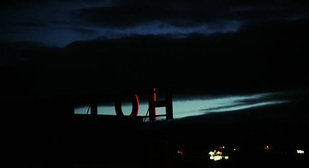 Signboard On Silhouette Hotel At Night