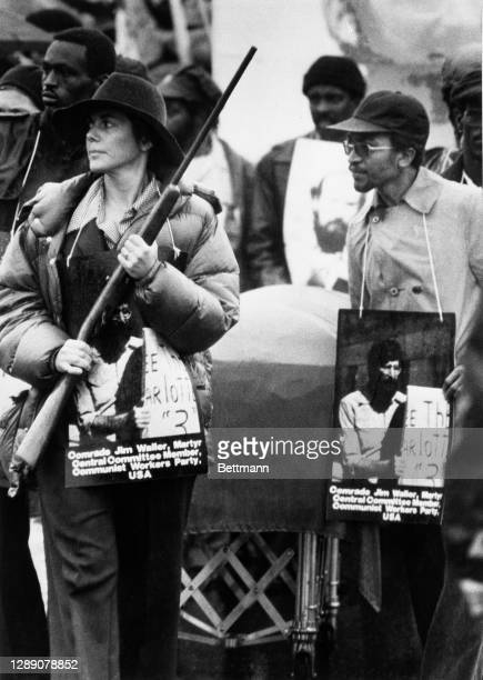 Signe Waller widow of Communist Party Worker Jim Waller carries a rifle during a funeral procession for five Party Workers, which included her...
