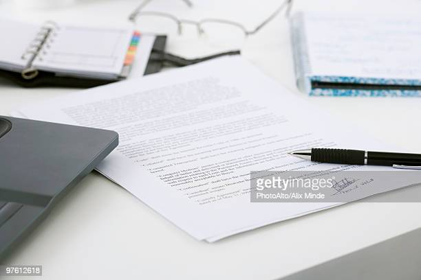 signed contract on cluttered desk - contrato imagens e fotografias de stock