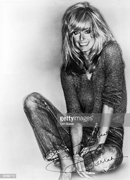 Signed promotional portrait of American actress Farrah Fawcett barefoot and in a knit sweater and jeans mid 1980s The signature reads 'Love and best...