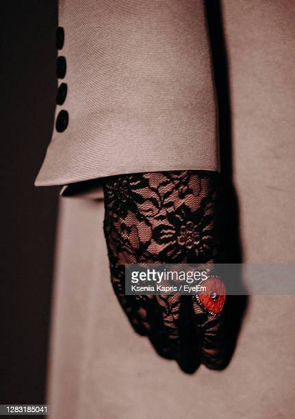 signet ring with red stone, lace and black gloves and beige women's coat with black buttons - lace glove stock pictures, royalty-free photos & images