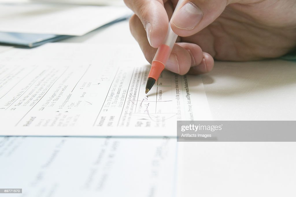 Signing a IRS tax form : Stock Photo