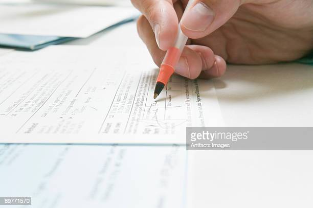 signing a irs tax form - form filling stock pictures, royalty-free photos & images