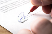 Signing contract, lease or settlement for acquisition, apartment lease, insurance, bank loan, mortgage or business buyout. Man writing name and autograph with pen. The signature is made up.