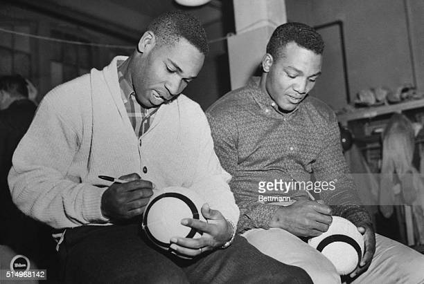 Signing footballs instead of carrying them crack Cleveland Browns' backs Bobby Mitchell and Jim Brown autograph pigskins in the dressing room...